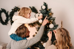 Happy family with child decorate christmas tree. Little girl sitting on daddy's shoulders hangs ball on the Christmas tree