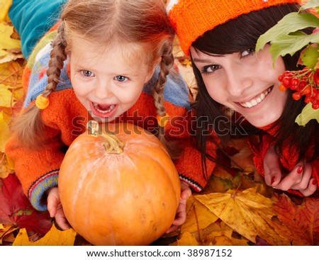Happy family with child on autumn orange leaf, pumpkin.Outdoor.