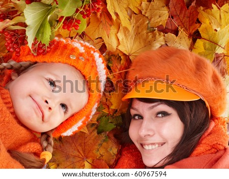 Happy family with child on autumn orange leaves. Outdoor.