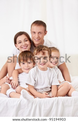 Happy family with children in bed