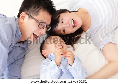 Happy family with children in bed, asian people