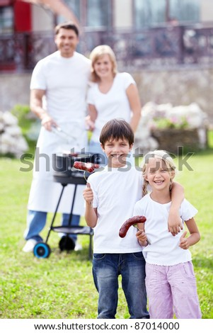 Happy family with children make barbecue