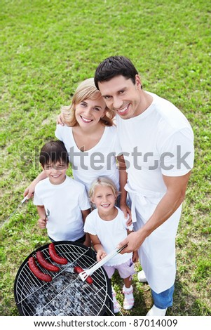Happy family with children make barbecue - stock photo