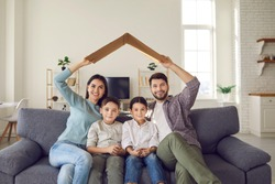 Happy family with children sitting at home on the couch under a symbolic cardboard roof. Family feels happy in their new apartment. Concept of buying a new home and its insurance.