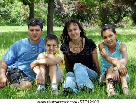happy family with children sitting on green grass in park