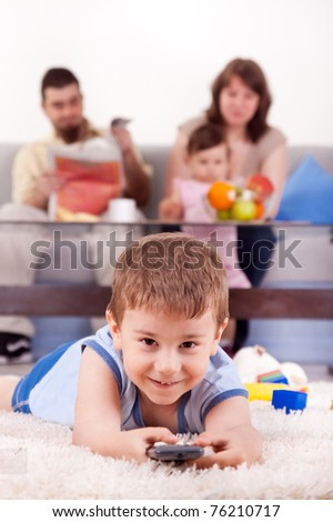happy family with children sitting on sofa and  watching TV at home