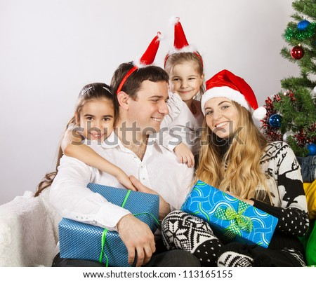 Happy family with Christmas presents near the Christmas tree