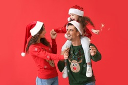 Happy family with Christmas sparklers on color background