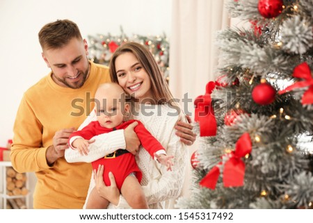 Happy family with cute baby near decorated Christmas tree at home