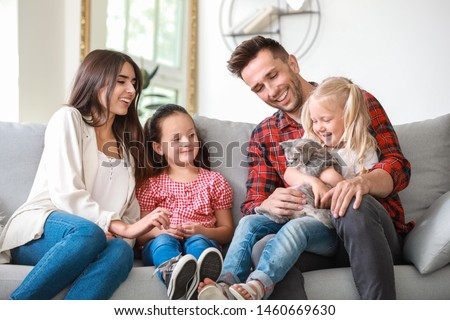 Happy family with cute cat resting at home ストックフォト ©