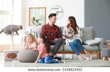 Happy family with cute cats resting at home ストックフォト ©