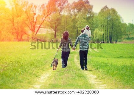 Happy family with dog walking on the rural dirt road. Little girl sitting on dad's shoulder stock photo