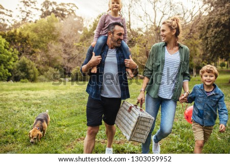 Happy family with dog walking towards the picnic spot in the garden. Man carrying his daughter on shoulders with woman holding son hand and carrying a picnic basket.