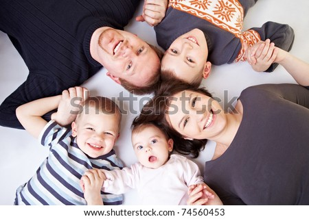 Happy family with father and mother and three children including baby girl