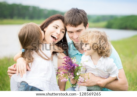 Happy family with flowers having fun outdoors in spring field