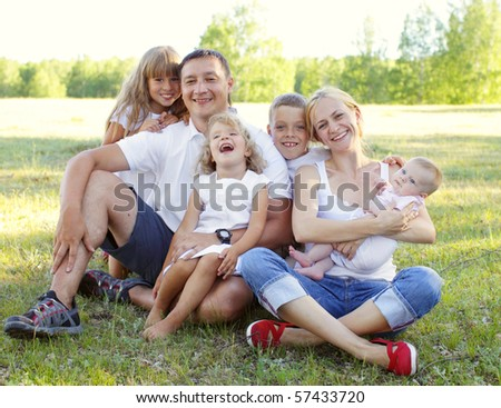 Happy family with four children in park - stock photo