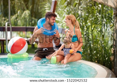 Happy family with kid enjoying in swimming pool