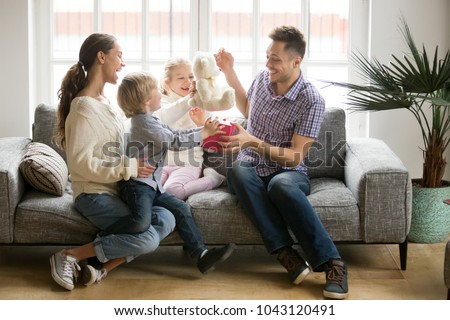Happy family with kids congratulate excited dad with fathers day, wife with little son and daughter presenting gift for daddy holding present box making surprise, children greeting parent on birthday