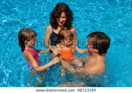 Happy family with kids in swimming pool. Smiling parents and children on summer vacation