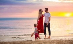 Happy family with kids on tropical beach. Sea vacation. Parents and children walking at ocean shore at sunset. Summer fun. Travel with baby and young child. Mother, father, son and daughter playing.