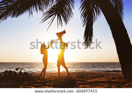Happy family with little daughter having fun under palm tree on sunset beach background. Father tossing daughter #606897455