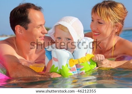 Happy family with little girl in white hat and life-jacket bathing in pool against sea, Parents looking against each other