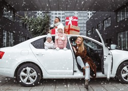 Happy family with new year presents and Christmas tree. Dad, mom and two daughters are going for Christmas holidays by car. Xmas shopping and preparation