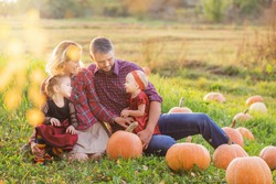 happy family with orange pumpkins in autumn field