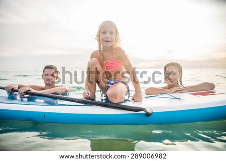Happy family with paddle board swimming in the ocean - Pretty young girl smiling while learning to paddle - Portrait of active and sportive family on vacation on summertime