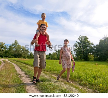 Happy family with pregnant woman, kid and father walking on the road