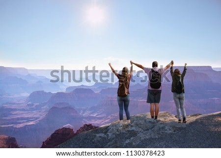 Happy family with raised hands enjoying time together  on top of the  mountain. South Rim, Grand Canyon National Park, Arizona,  USA. #1130378423