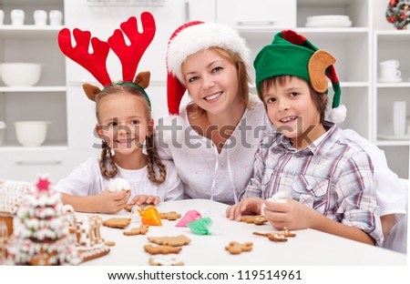 Happy family with seasonal hats decorating christmas gingerbread cookies