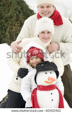 Happy family with snowman - stock photo