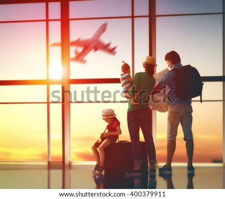 Shutterstock Happy family with suitcases in the airport.