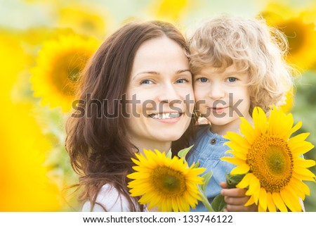 Happy family with sunflowers having fun outdoors in spring field