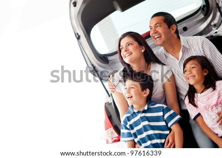 Happy family with their new car smiling