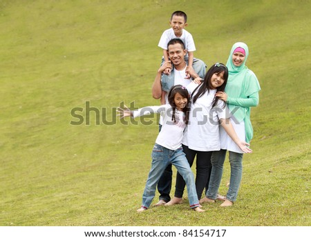 Happy family with three children. Father, mother, daughters and son in the park