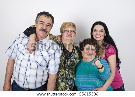 Happy family with  three generations of women grandmother,mother ,daughter and father  posing in a big embrace ,elderly woman pointing to you