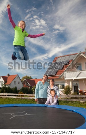 Happy family with trampoline outside house with solar panels