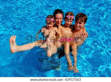 Happy family with two children having fun in swimming pool