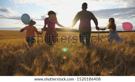 Happy family with two children holding hands of each other and running through wheat field at sunset. Young couple of parents with kids jogging among barley meadow and enjoying nature together. ストックフォト ©