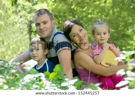 Happy family with two children sitting in grass