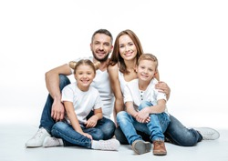 Happy family with two children sitting together and looking at camera isolated on white