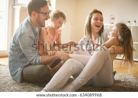 Happy family with two daughters playing at home. Family sitting on floor and playing together. #634089968