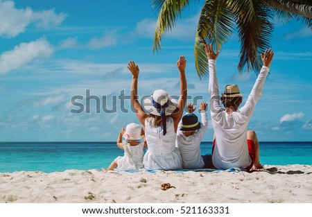 Photo of  happy family with two kids hands up on the beach