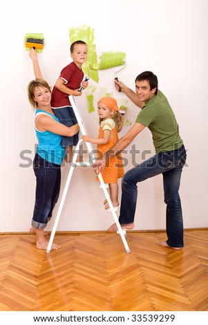Happy family with two kids holding brushes and painting rolls redecorating their home together