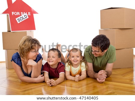 Happy family with two kids in their new home laying on the floor among cardboard boxes