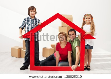 Happy family with two kids moving into their new home - sitting among cardboard boxes - stock photo