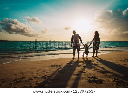 happy family with two kids on play on sunset beach