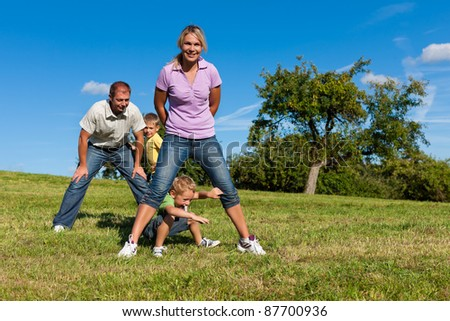 Happy family with two little boys playing in the grass on a summer meadow